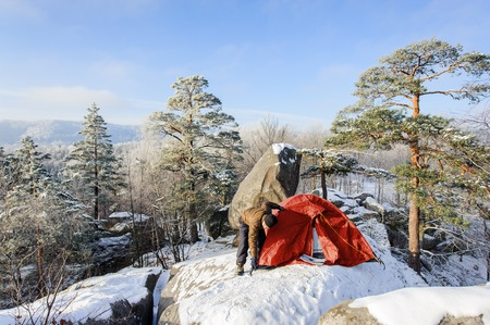 Young man hiker is putting up his red tent on a big rock at the winter mountain base camp on a cold sunny day. Winter camping. Winter hiking equipment.