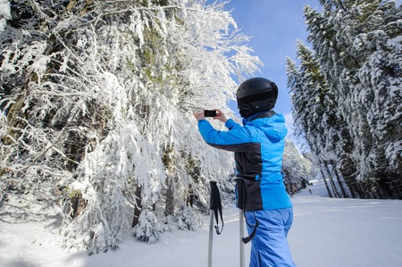 thrilling: Rear view of skier in the winter forest on ski slope taking picture with her cell phone. Winter sports concept. Stock Photo