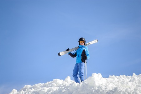 wintersport: Skier standing on top of the mountain against blue sky on a sunny day. Girl is holding skis on her shoulder smiling and looking into the camera. Winter sports concept. Carpathian Mountains