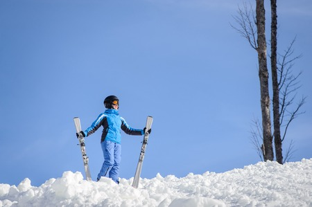 wintersport: Young female skier wearing blue ski suit helmet and goggles on sunny day. Woman is holding her skis. Winter sports concept.