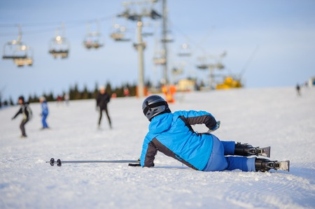 Young woman skier in blue ski suit after the fall on mountain slope trying get up against ski-lift. Ski resort. Winter sports concept.