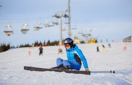 Young woman skier in blue ski suit getting up after the fall on mountain slope against ski-lift. Ski resort at Carpathian Mountains, Bukovel. Winter sports concept.