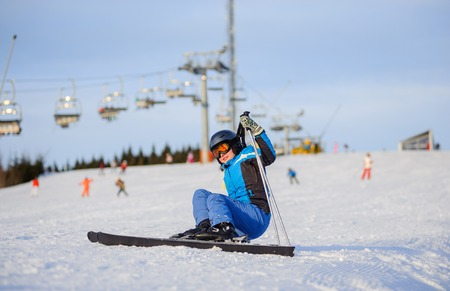 levantandose: Young female skier in blue ski suit getting up after the fall on mountain slope against ski-lift. Ski resort. Winter sports concept. Foto de archivo