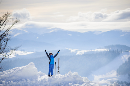 arms lifted up: Happy woman skier standing on the top of the mountain with her arms lifted up against the background of beautiful winter mountains.