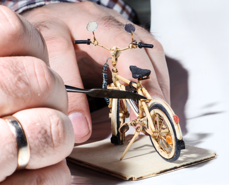 Miniature of wooden bicycle on white background. Handcrafting process, craftsmans hand holding the tool. Macro shot.