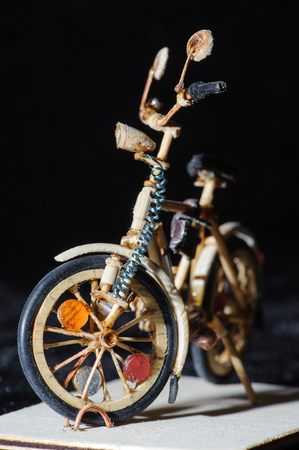 Miniature handicraft of wooden bicycle on black background. Macro shot. Frontal view Stock Photo