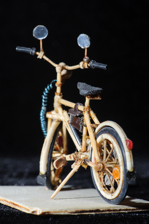 Miniature handicraft of wooden bicycle on black background. Macro shot. Rear view Stock Photo