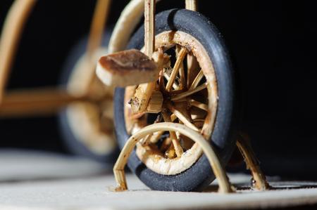 Miniature handicraft detail shot of wooden bicycle on black background. Macro shot of front wheel. Stock Photo