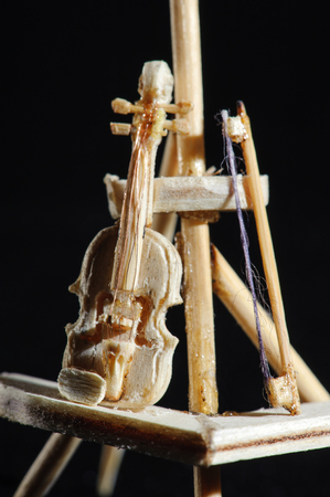 Wooden miniature of violin on black background. Violin standing on wooden stand. Super macro shot.