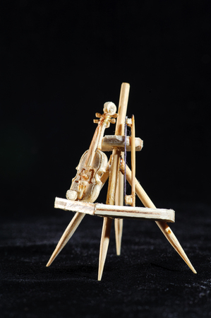 Wooden miniature of violin and stick on black background. Violin standing on wooden stand. Macro shot. Stock Photo
