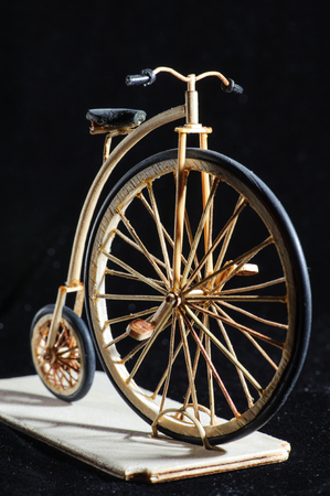Wooden miniature of penny-farthing bicycle on black background. Old School bike with a big front wheel. Macro shot. Stock Photo