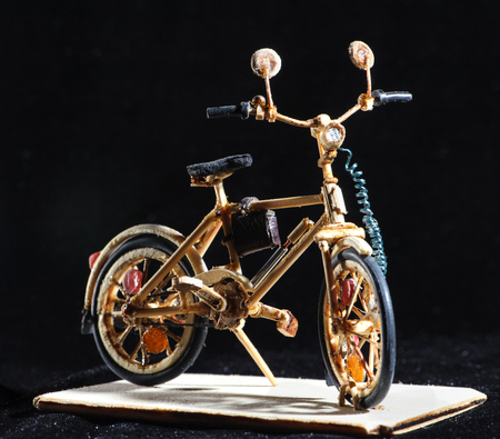 Miniature handicraft of wooden bicycle on black background. Macro shot.