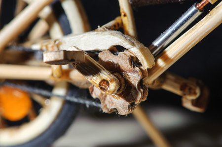 Miniature handicraft detail shot of wooden bicycle on black background. Macro shot of pedal.