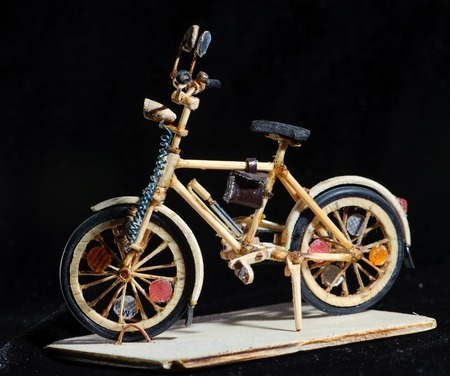 Miniature handicraft of wooden bicycle on black background. Macro shot. Side view