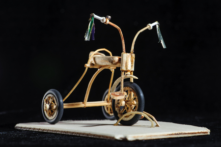 Miniature of wooden kids bicycle on black background. Macro shot. Front view Stock Photo