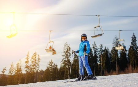 thrilling: Full length portrait of young female skier against ski-lift and forest on a sunny day. Woman is wearing helmet skiing glasses gloves and blue ski suit. Ski resort at Carpathian Mountains, Bukovel