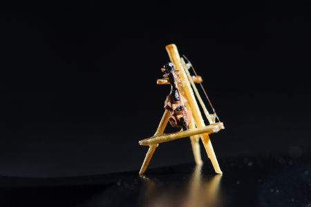 Wooden miniature of violin on black background. Violin standing on wooden stand. Macro shot.