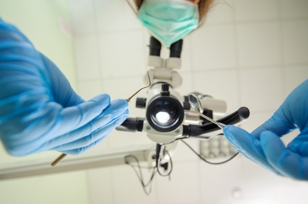 Low angle view of dentist holding dental probe and mirror and looking through the microscope. Focus on dental tools. First person view. Dentist wearing mask and gloves Stock Photo