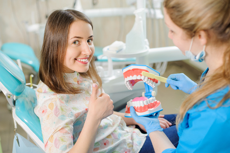 Woman dentist showing dental jaw model to female patient in dentists office. Beautiful smiling lady at dentist sitting in dentist chair and giving thumb up. Stock Photo