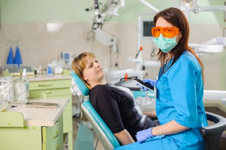 Female dentist is holding dentist photopolymer lamp getting ready to treat patient in clinic. Doctor is wearing gloves and glasses. Stomatology equipment.