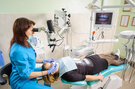 scaler: Female dentist working with microscope at modern dentist clinic. Doctor checking female patient teeth looking in dental mirror through the microscope. Teeth care and tooth health. Dental equipment Stock Photo