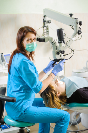 Portrait of woman dentist working with microscope at modern stomatological clinic. Teeth care and tooth health. Medical equipment