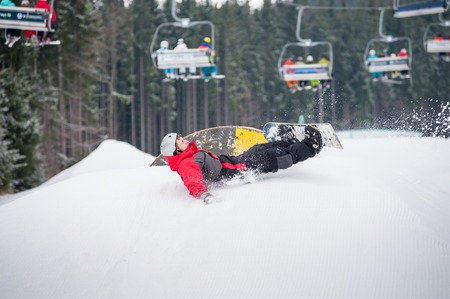 flight helmet: Male snowboarder falls on the slopes during the jumping with ski lifts in background, extreme sport Stock Photo