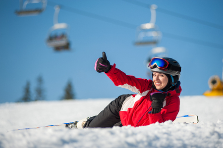 Happy female skier lying with skis on snowy at mountain top, showing thumb up gesture of good class and looking at the camera in sunny day at a winter resort with ski lifts and blue sky in background