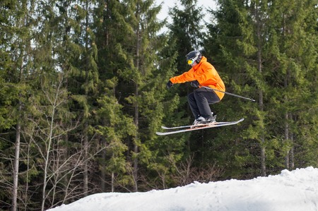 flight helmet: skier male flying at jump from the slope of mountains in orange jacket performing a high jump and looking apprehensive about the landing with forest in background. Side view