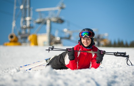 Smiling woman lying with skis on snowy at mountain top, holding ski-sticks and looking to the camera in sunny day at a winter resort with ski lifts and blue sky in background. Close-up