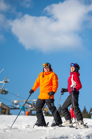 Couple holding skis smiling on mountain top together at a winter resort with ski lifts and blue sky in background. Man is wearing orange jacket, female in red jacket, both is wearing helmet and goggles. Reklamní fotografie