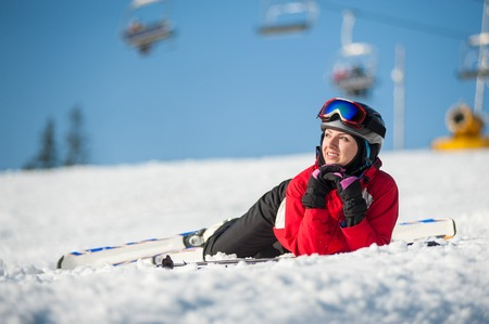 Portrait of smiling female skier lying with skis on snowy at mountain top in sunny day, having fun at a winter resort, ski lifts and blue sky in background