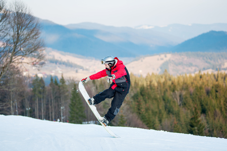 flight helmet: Man standing on his snowboard and taking his for the edge on top of a mountain against the backdrop of mountains, hills and forests in the distance.