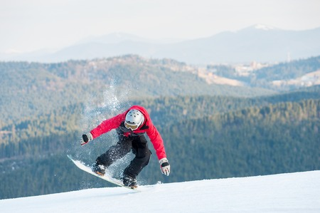 Snowboarder standing on his snowboard and taking his for the edge on top of a mountain against the backdrop of mountains, hills and forests in the distance. Stock Photo