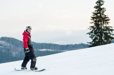 tightened: Smiling snowboarder wearing helmet, red jacket, gloves and pants standing on top of a mountain and looking at the camera near a lonely pine on the background of hills and the sky, tightened white cloud
