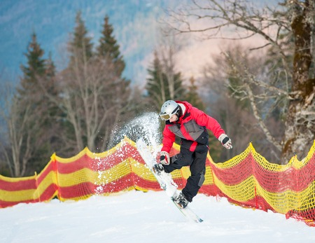 flight helmet: Snowboarder guy in action into snow powder at the mountains on background  forest, hills and yellow and red fence. Extreme freeride. Ski resort, Carpathian mountains Stock Photo