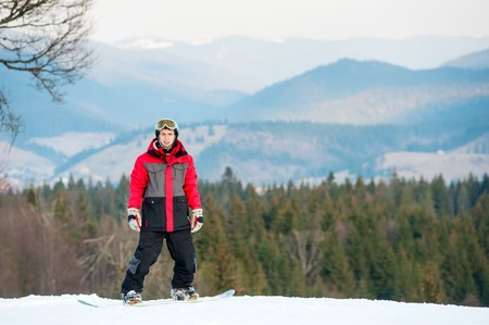 Portrait of snowboarder wearing helmet, red jacket, gloves and pants standing on top of a mountain and looking at the camera on the background of forests, hills and the sky