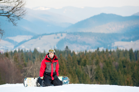 Young snowboarder wearing helmet, red jacket, gloves and pants resting on ski slope, kneeling and looking at the camera on the background of beautiful mountains and forests, winter sports concept