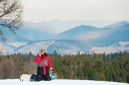 Man snowboarder wearing helmet and mask resting on ski slope, hes kneeling and talking on the phone on the background of beautiful mountains and forests, winter sports concept. Stock Photo