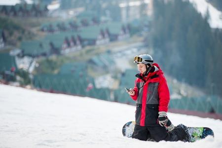 Young snowboarder resting on ski slope, hes kneeling, looking on the phone, winter sports concept. Ski resort Reklamní fotografie