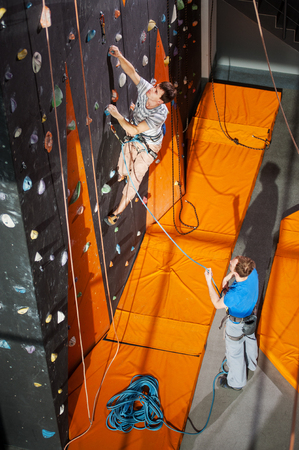 belay: Strong climber is climbing on an indoor rock-climbing wall, his partner standing on the ground belaying the climber