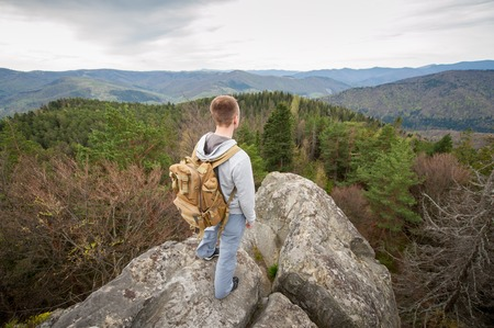 wide angle lens: Tourist male with a brown backpack standing on the top of the  rock, back to the camera and looking into the distance on the green forest and nice mountains. View from above. Wide angle lens Stock Photo