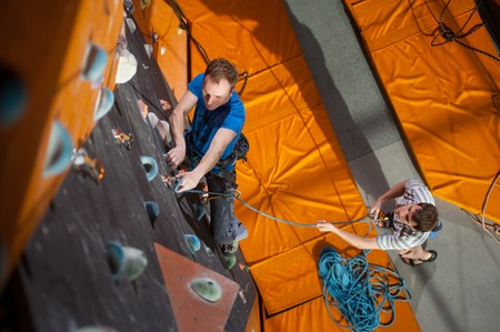 belay: Strong man practicing climbing on rock wall indoors, view from above. Man standing on the ground insuring the climber Stock Photo