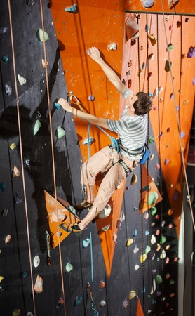 belay: Athletic young male climber practicing rock-climbing on a rock wall indoors Stock Photo