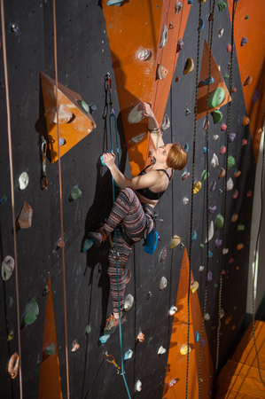 belay: Young woman climber is climbing up on indoor climbing wall and looking up