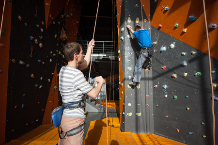 belay: Guy holding a rope with belay device and belaying the climber on rock wall indoors