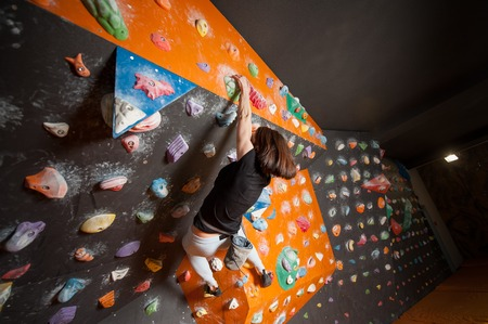 steep: Young female climber is climbing up on practicing rock wall indoor