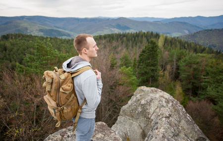 Portrait of young tourist with backpack stands on top of the rock, back to the camera and looking into the distance. Green dense forest and mountains in background. Close-up Stock Photo