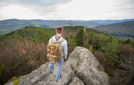 Young male tourist with a backpack standing on the edge of a rock and looking into the distance on the green forest and nice mountains Stock Photo