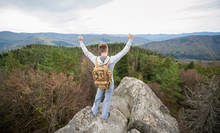 Man traveler with a backpack standing on mountain top, with back to the camera with hands up, against picturesque view of on the green forest and nice mountains. View from above